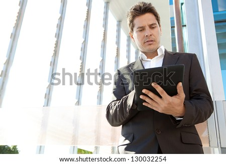 Portrait of a senior businessman standing by a modern architecture glass office building in the city, using a digital technology tablet pad. - stock photo