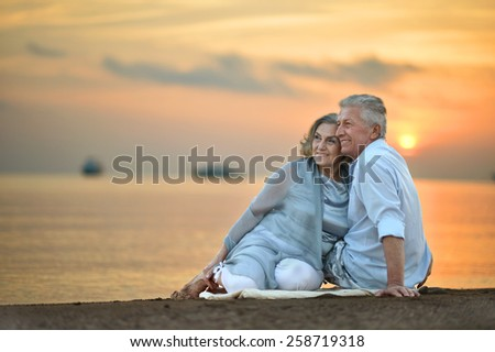Portrait of a senior couple at sea at sunset - stock photo