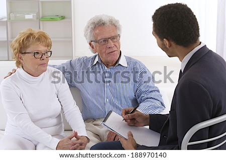 Portrait of a senior couple discussing with a young consultant ( could be a insurance sales agent or financial planner) - stock photo