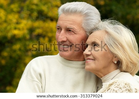 Portrait of a senior couple resting at autumn park