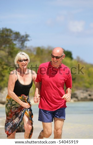 Portrait of a senior couple running on the beach - stock photo