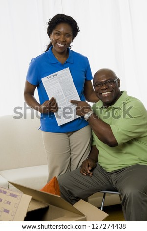 Portrait of a senior couple smiling and holding the deed to their new home