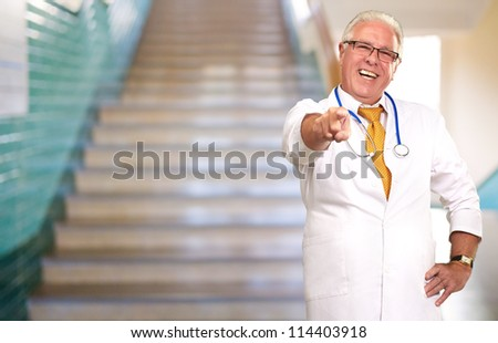 Portrait Of A Senior Doctor Pointing, Indoor - stock photo