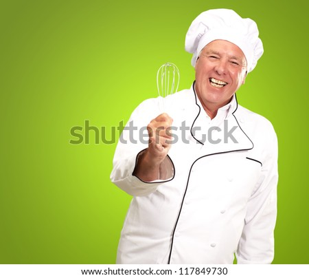 Portrait Of A Senior Male Chef Holding A Beater On Green Background - stock photo