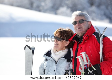 Portrait of a senior man and a senior woman smiling with skis in snow