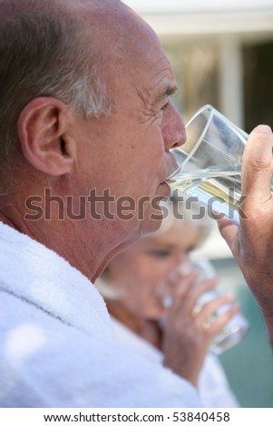 Portrait of a senior man drinking a glass of water - stock photo