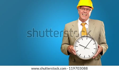 Portrait Of A Senior Man Holding A Wall Watch On Blue Background - stock photo