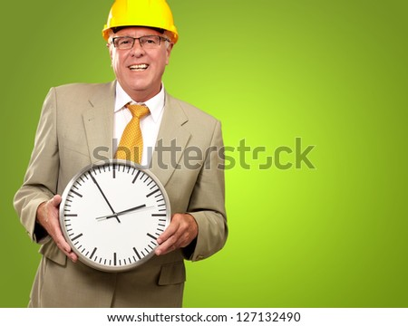 Portrait Of A Senior Man Holding A Wall Watch On Green, Background - stock photo