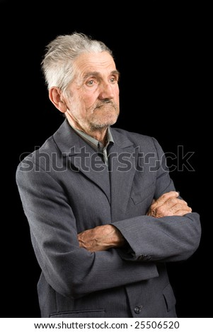 Portrait of a senior man in suit, isolated over black background - stock photo