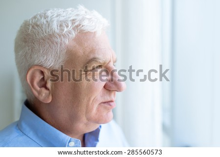 Portrait of a senior man looking through window