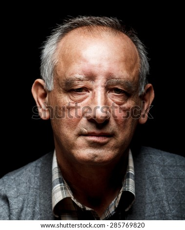Portrait of a senior man on black background, Front view - stock photo