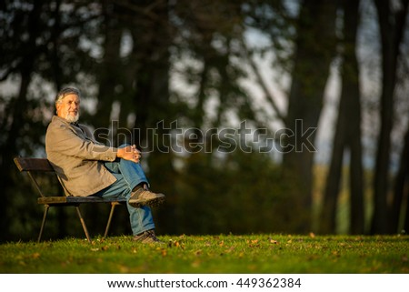 Portrait of a senior man outdoors, sitting on a bench in a park (shallow DOF; color toned image) - stock photo