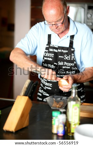 Portrait of a senior man peeling an onion - stock photo