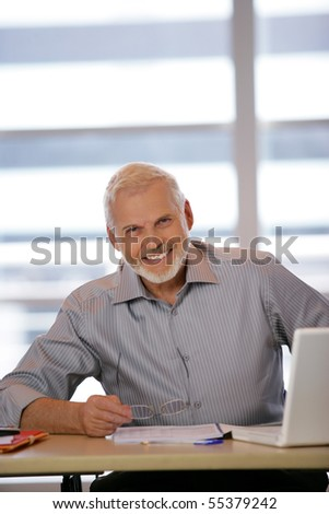 Portrait of a senior man sitting at a desk in front of a laptop computer - stock photo