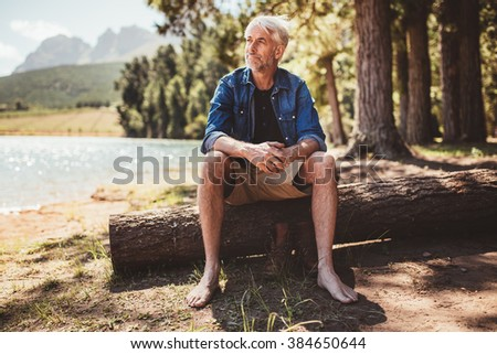 Portrait of a senior man sitting on a log near lake and looking away. Mature man sitting alone on lake. - stock photo