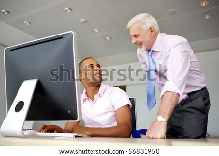 Portrait of a senior man smiling and a young man sitting in front of a desktop computer - stock photo