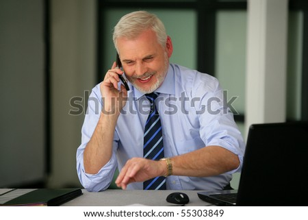 Portrait of a senior man smiling in suit with a phone and a laptop computer - stock photo