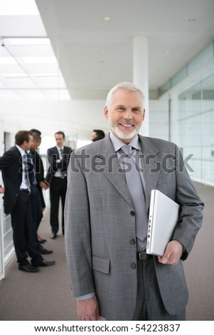 Portrait of a senior man smiling with a laptop computer
