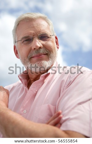 Portrait of a senior man smiling with eyeglasses - stock photo