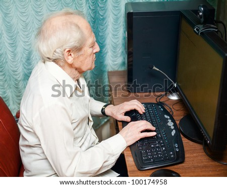 portrait of a senior man typing something on his computer - stock photo