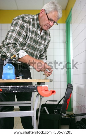 Portrait of a senior man with a blowtorch - stock photo