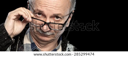 Portrait of a senior man with glasses on black background with copy-space - stock photo