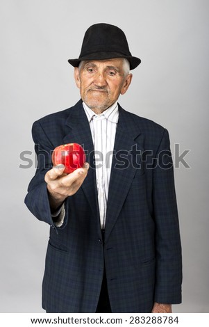 Portrait of a senior man with hat holding a red apple over grey background - stock photo