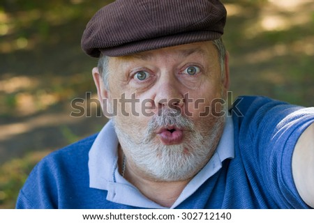 Portrait of a senior man wondering and making first selfie in his life - stock photo