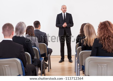Portrait Of A Senior Manager Giving Presentation To His Colleagues - stock photo