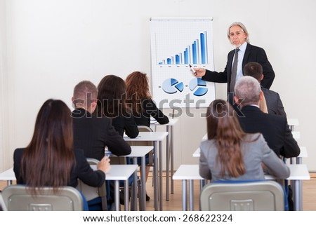Portrait Of A Senior Manager Giving Presentation To His Colleagues At Office - stock photo