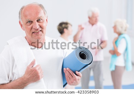 Portrait of a senior participant of fitness classes, with a white towel on his shoulder, holding an exercise mat