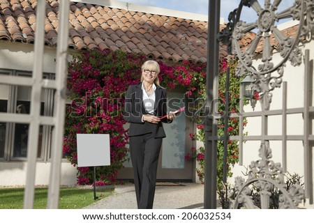 Portrait of a senior real estate agent walking with clipboard - stock photo
