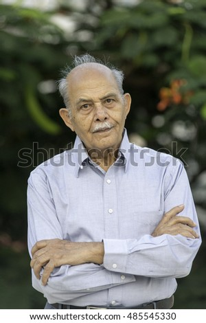 Portrait of a senior South Asian man outdoors looking to camera
