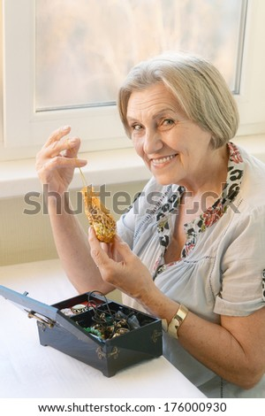 Portrait of a senior woman at home with jewelries