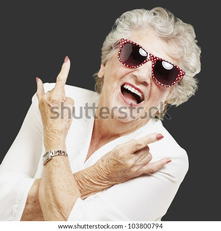 portrait of a senior woman doing a rock symbol over a black background - stock photo