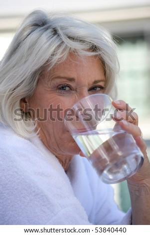 Portrait of a senior woman drinking a glass of water - stock photo