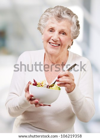 portrait of a senior woman eating a salad indoor