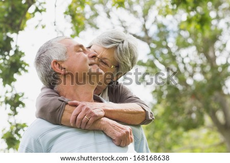 Portrait of a senior woman embracing man from behind at the park