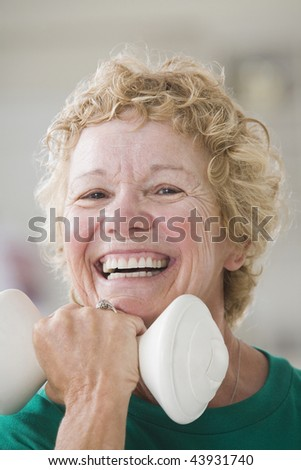 Portrait of a senior woman exercising with a hand weight - stock photo