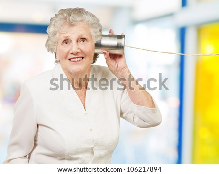 portrait of a senior woman hearing with a metal tin can indoor