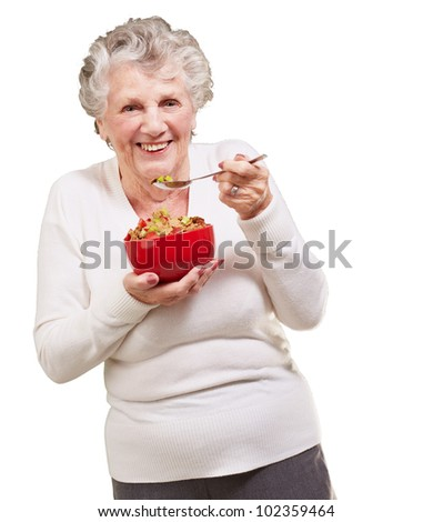 portrait of a senior woman holding a cereal bowl against a white background - stock photo