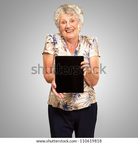 Portrait Of A Senior Woman Holding A Digital Tablet On grey Background