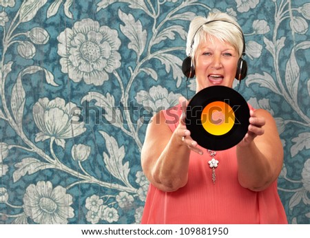 Portrait Of A Senior Woman Holding A Disc On Wallpaper - stock photo