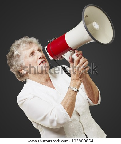 portrait of a senior woman holding a megaphone over a black background - stock photo