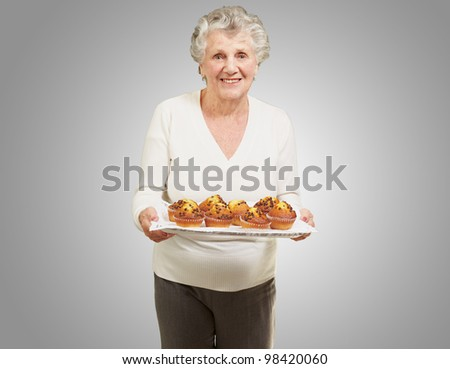 portrait of a senior woman holding a tray with muffins against a grey background - stock photo