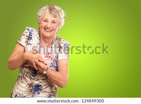 Portrait Of A Senior Woman Holding Popcorn Box On Green Background - stock photo
