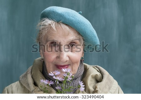 Portrait of a senior woman in green beret, holding flowers with a happy look at her face, outdoor shot