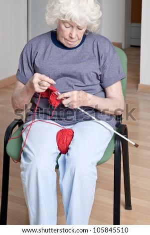 Portrait of a senior woman knitting. - stock photo