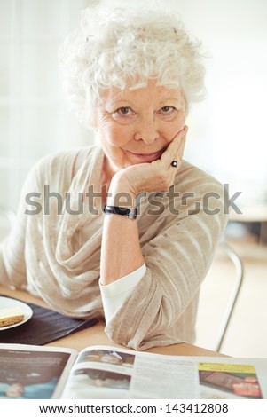 Portrait of a senior woman looking at you with hand on chin - stock photo