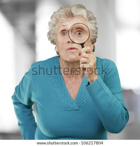 portrait of a senior woman looking through a magnifying glass, indoor - stock photo